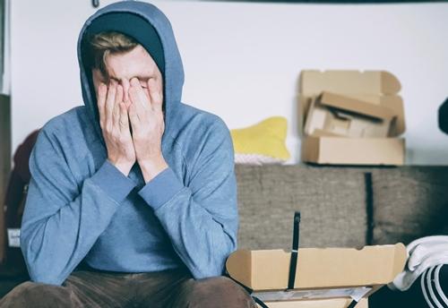 Dečko sedi na kauču i drži se za glavu