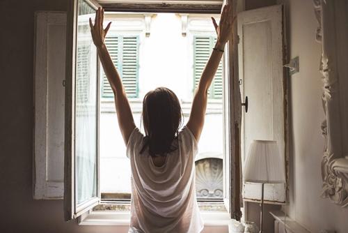 Devojka se isteže na prozoru