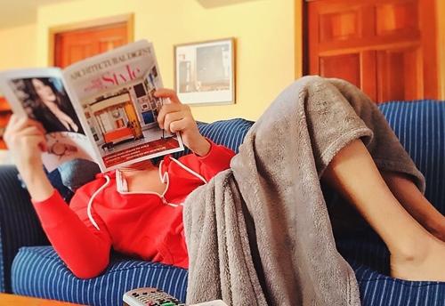 Devojka leži na kauču i čita magazin