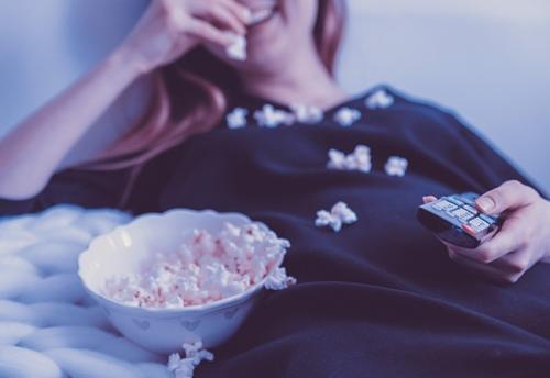 Devojka leži, jede kokice i gleda televizor