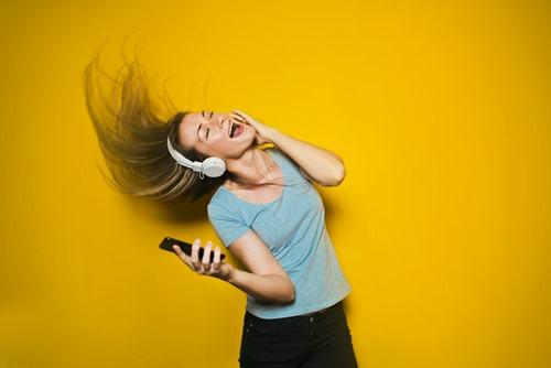 Devojka sluša muziku i igra
