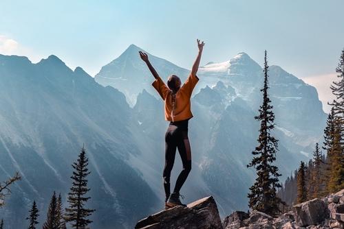 Devojka stoji na vrhu planinte