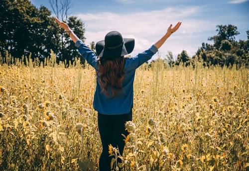 Devojka raširenih ruku na polju